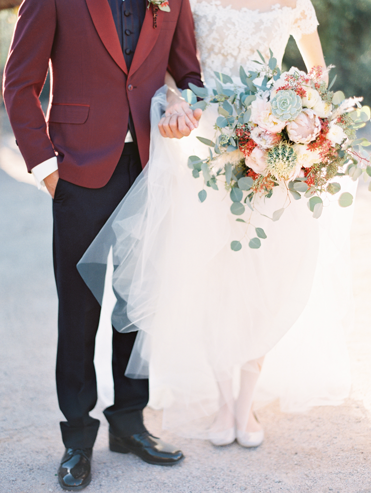 Groom i a red jacket and bride with a wild, desert bouquet. Dreamy wedding inspo