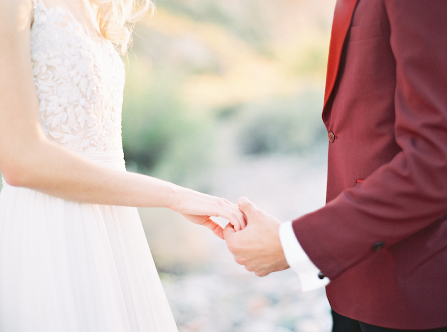 Groom in a red tux jacket takes his bride's hand. Pretty lace wedding dress