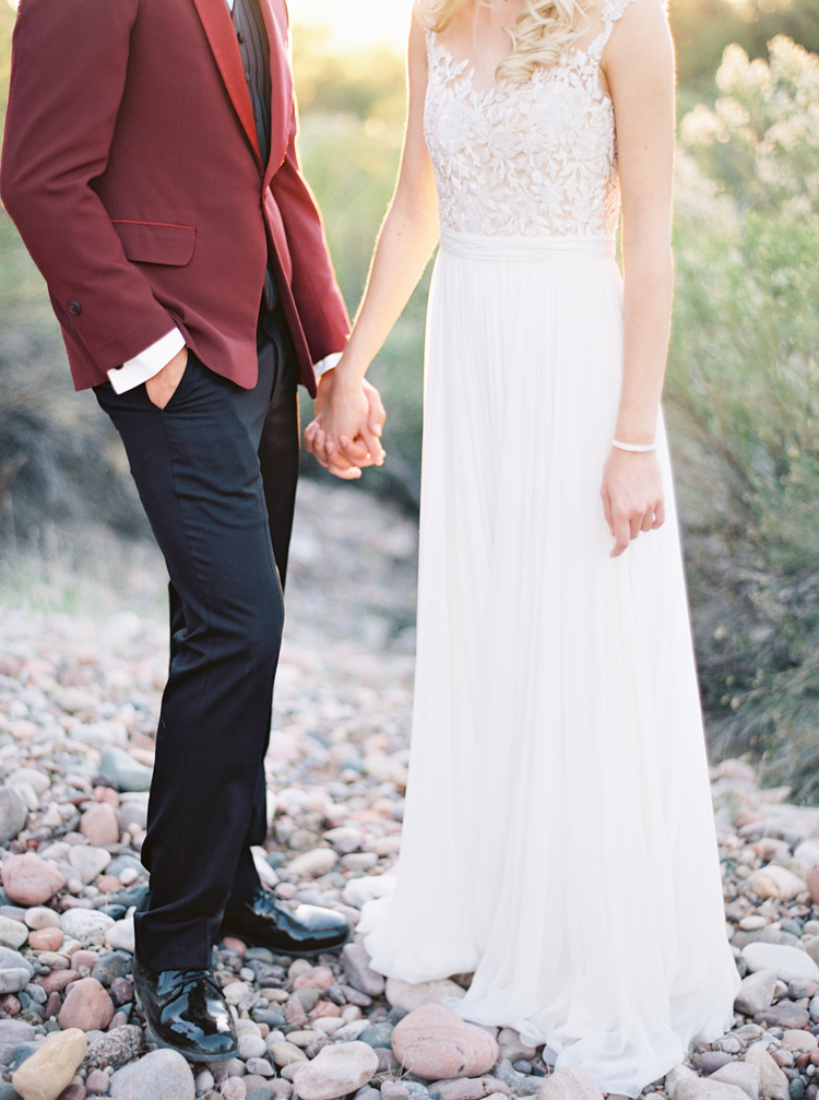 Groom in a red tux jacket.  Wedding dress with a lace bodice and softly flowing skirt.