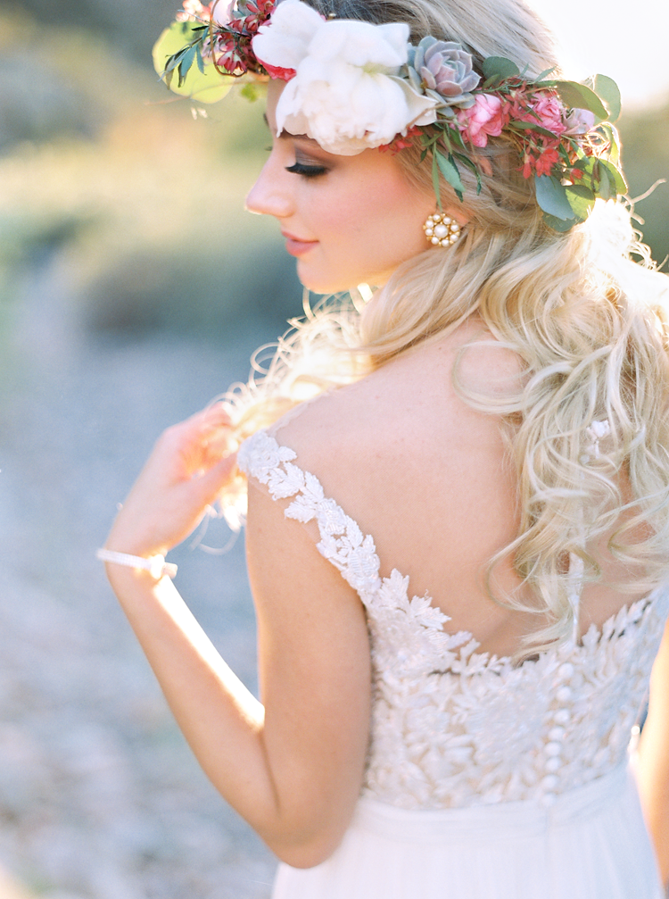 Bride in a flower crown decked with succulents, wearing a pretty lace wedding dress