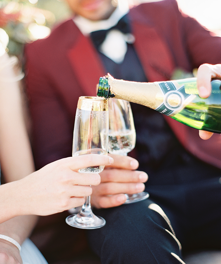 A groom pours champagne into an elegant gold-edged flute for his bride.