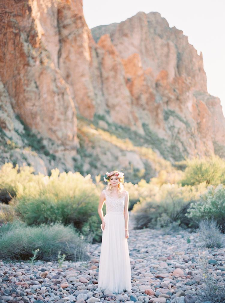 Bride in a flower crown decked with succulents, wearing a pretty lace wedding dress in the desert