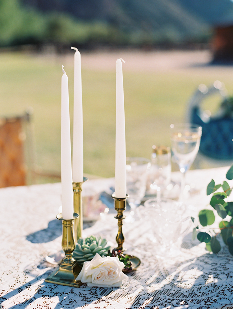 Brass candlesticks and a lace tablecloth for an eclectic and pretty reception table. Wedding inspo