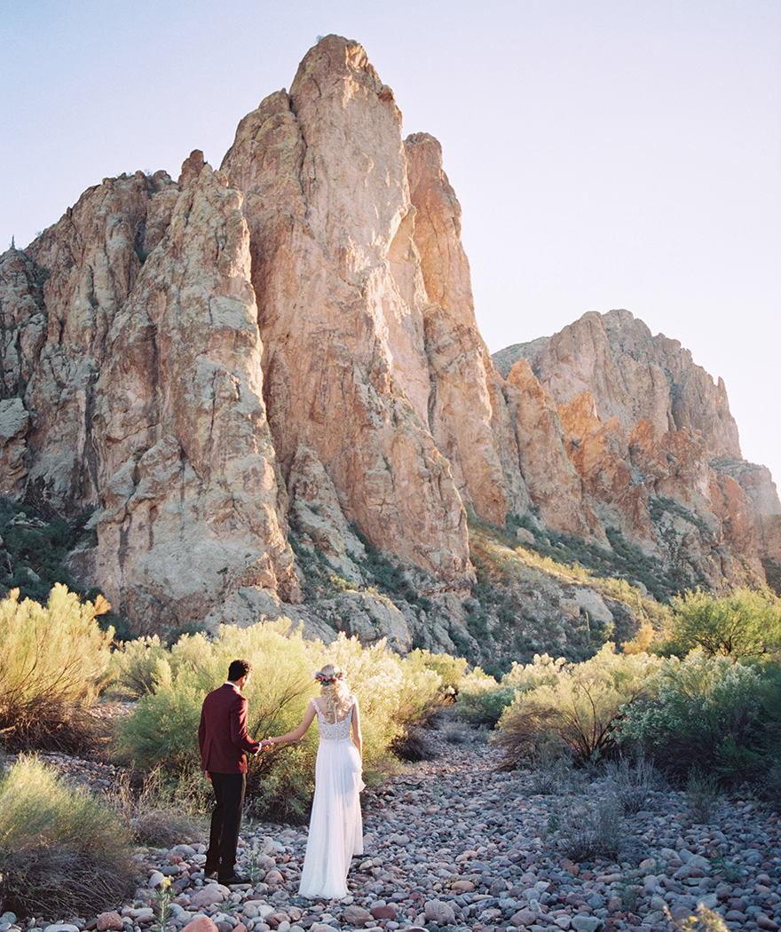 Desert wedding inspiration. Groom in red and bride with a flower crown.