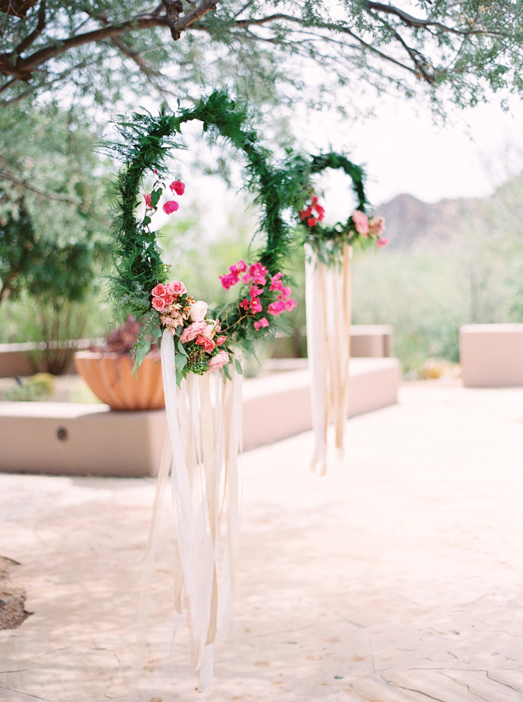 Wreaths of greenery & flowers with fluttering silk ribbons for a dreamcatcher look. Outdoor wedding