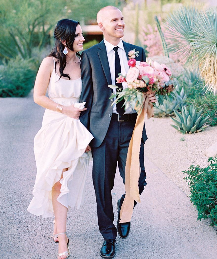 Smiling bride & groom at Four Seasons Scottsdale at Troon North. Lavish pink bouquet w/ silk ribbons