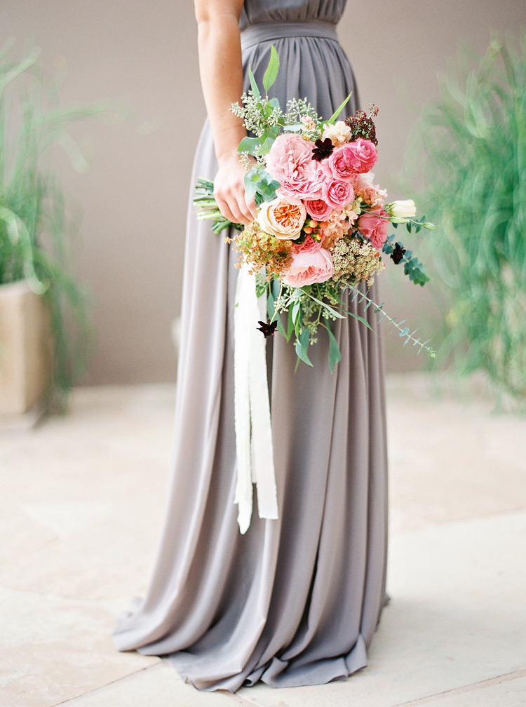 Bridesmaid in gray draped dress from Paper Crown, designed by Lauren Conrad. Lush pink bouquet
