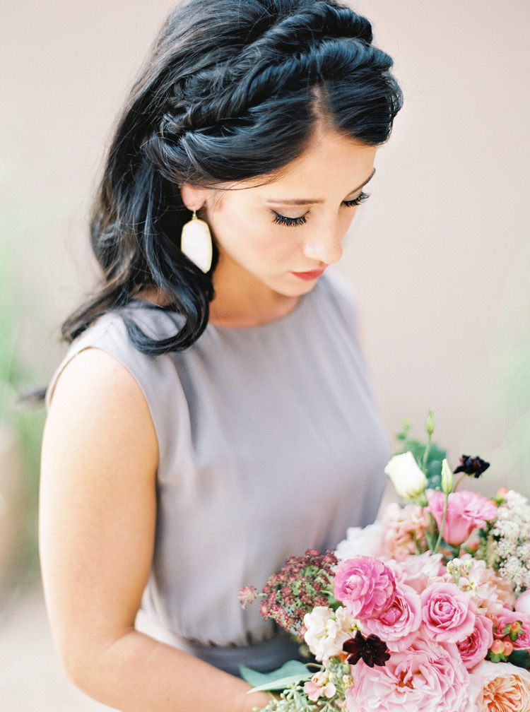 Elegant rolled crown hairstyle for a chic, bohemian bridesmaid. Gray, draped dress and pink flowers.