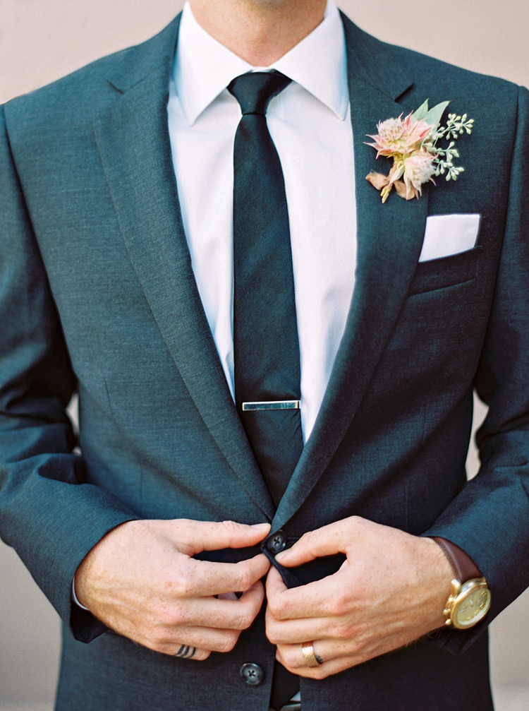 Stylish, modern groom in a close-cut suit. Unique boutonniere inspired by desert flowers.