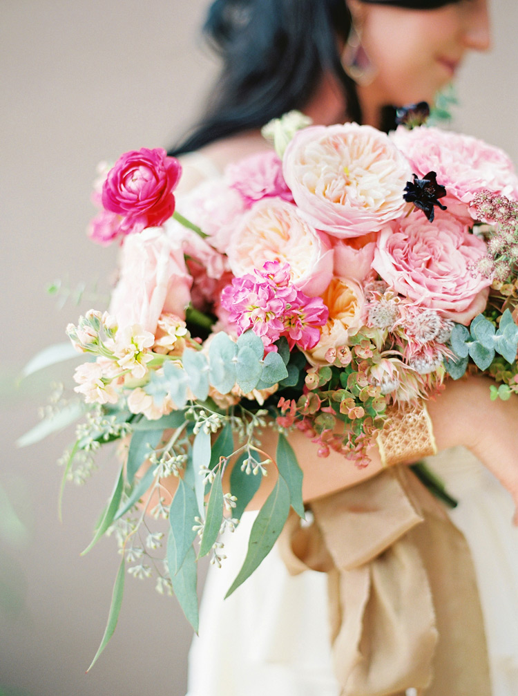An armful of rich pink flowers tied with a silk ribbon. Chic, bohemian bride with bouquet.