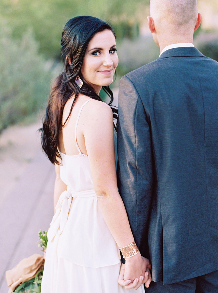 Chic, bohemian bride holds her groom's hand and looks back over her shoulder. Modern bridal style.