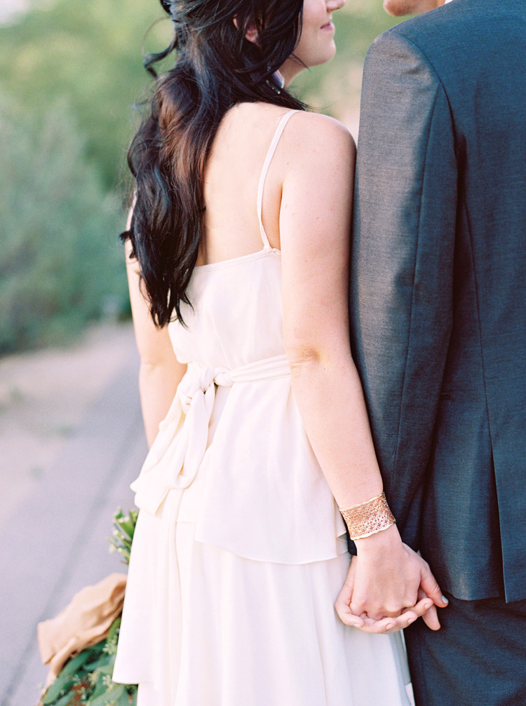 Chic, bohemian bride holds her groom's hand. Modern bridal style with classic Greek accents.