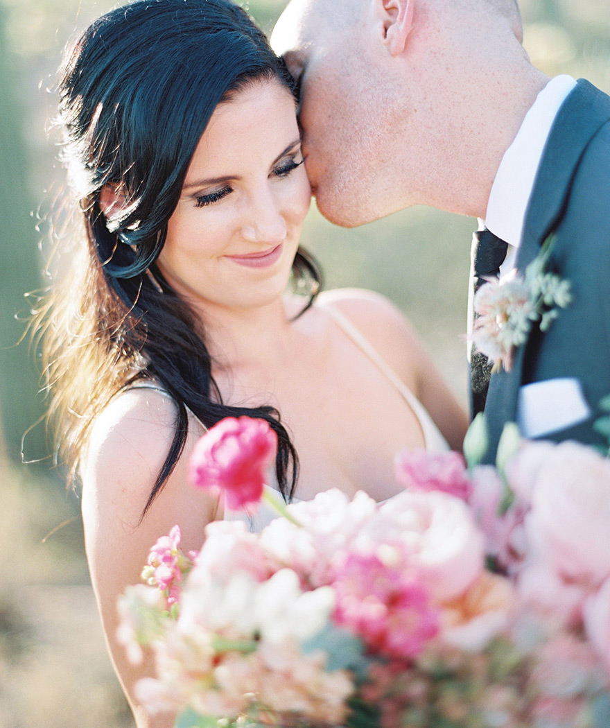 A groom steals a kiss from his bride. Modern, chic bridal style and a loose pink bouquet.