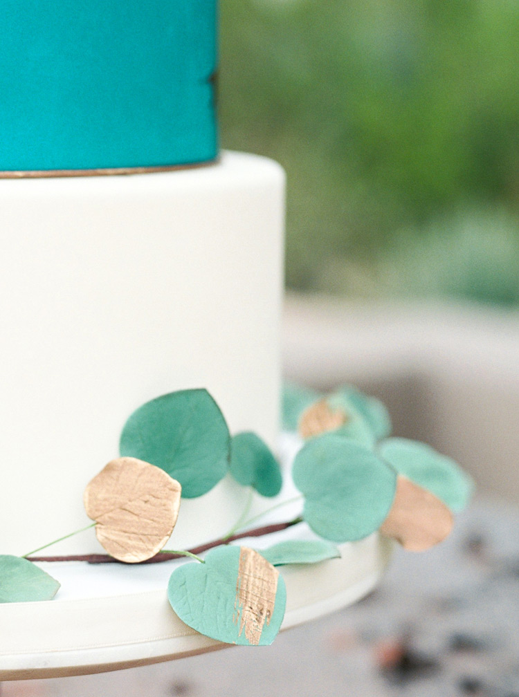 Leaves accented in gold decorate a modern Southwestern wedding cake.