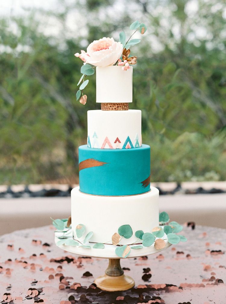 Modern Southwestern wedding cake with vivid turquoise tier and metallic accents/