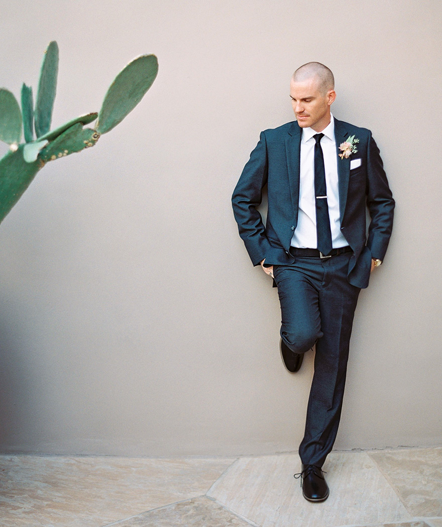 Stylish, modern groom in a close-cut charcoal suit with a long tie.