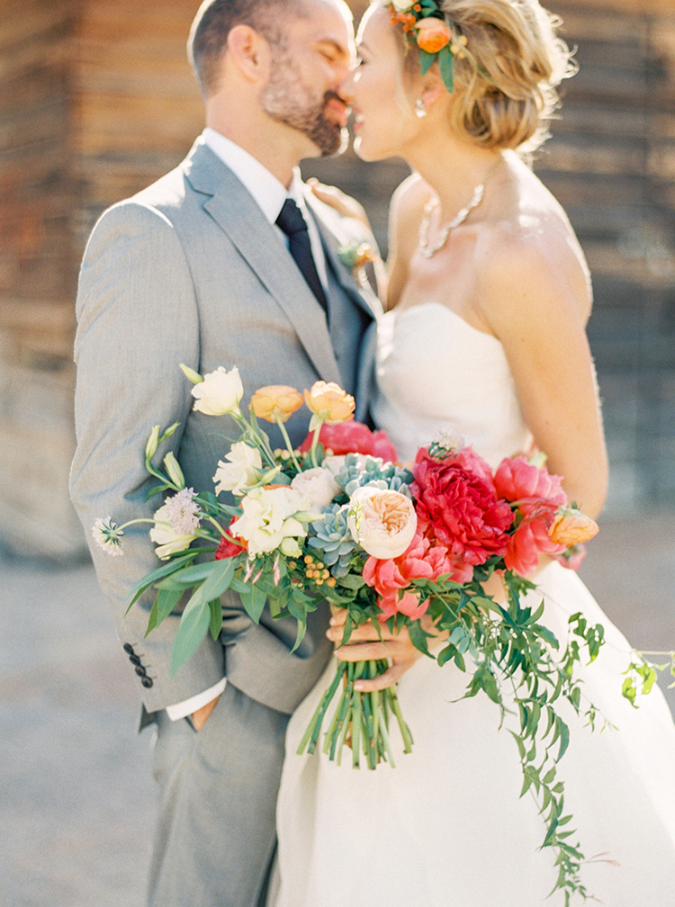 Bride And Groom Gently Kiss As Holds Flowy Bouquet
