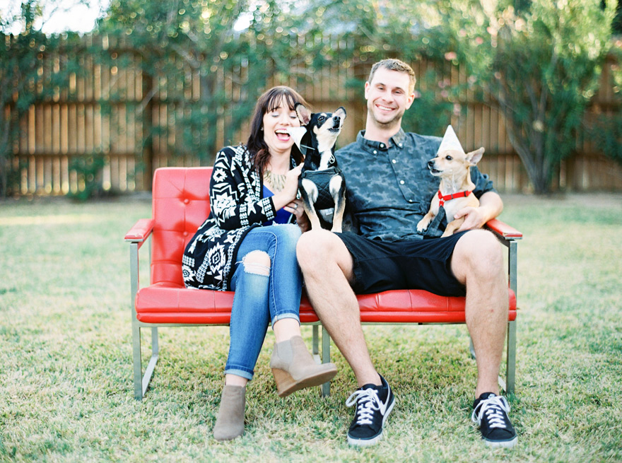 Family fun with two dogs barking outdoor. Posed in unique red couch.