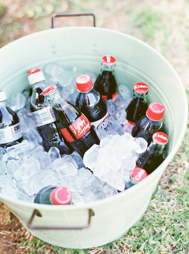 Birthday coke bottles in mint bucket.