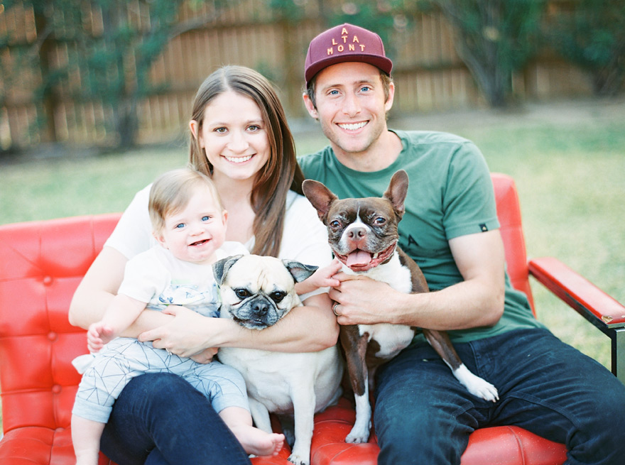 Sweet young couple and baby pose with two dogs on red sofa. Outdoor scenery.