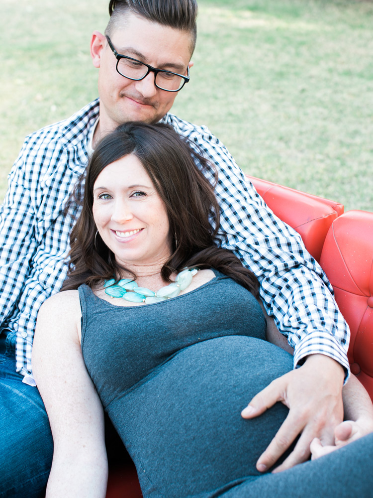 Husband embraces pregnant wife laying on red sofa. Sweet moment outdoors.