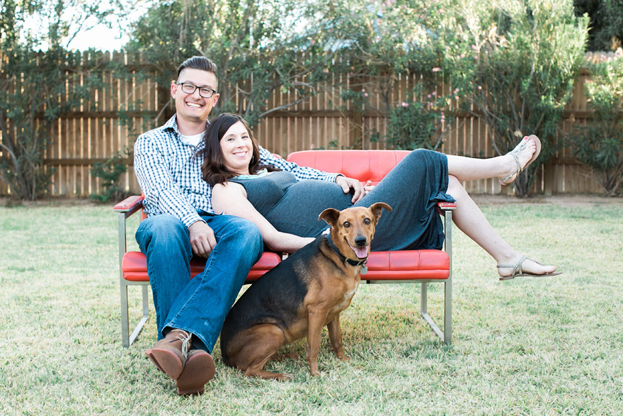 Couple lounging on red sofa with dog. Small family outdoors.