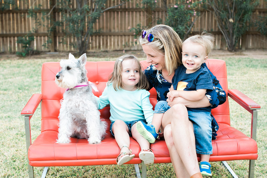 Mom laughing with sweet children and puppy on outdoor sofa.