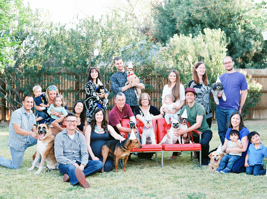 Outdoor gathering of friends and family with puppies.