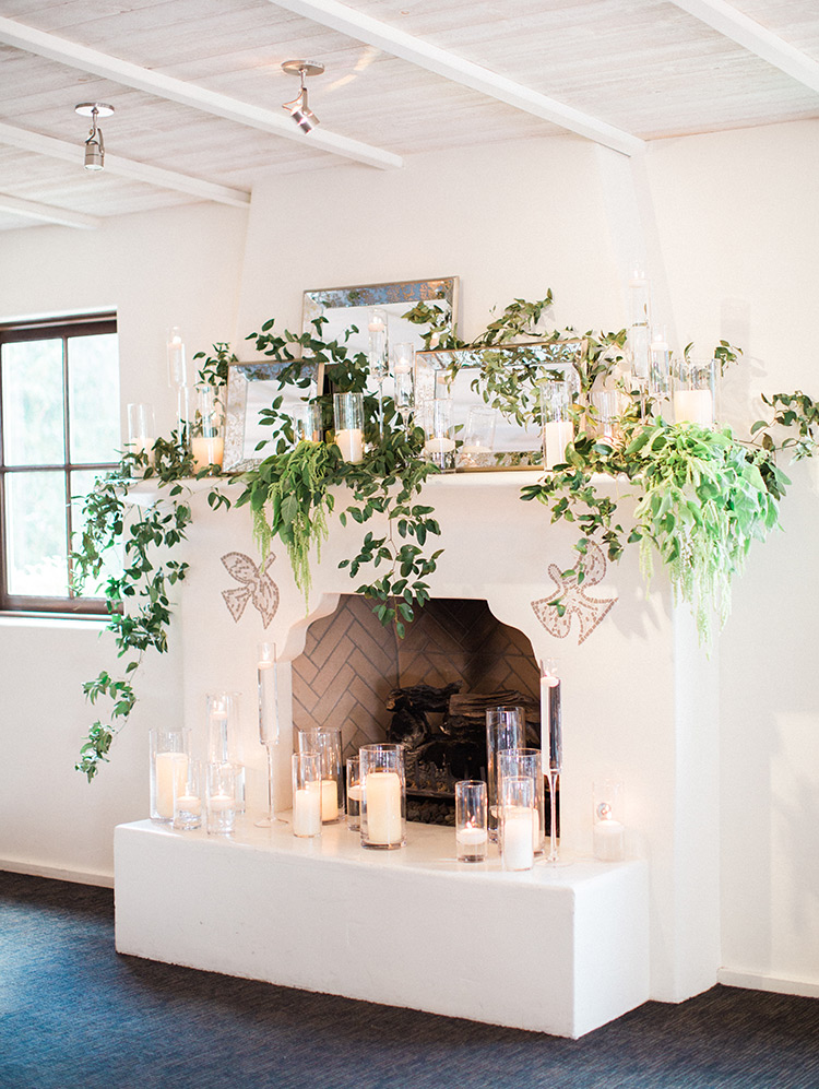 Mirrors, candles, and greenery decorate a mantle for a wedding reception