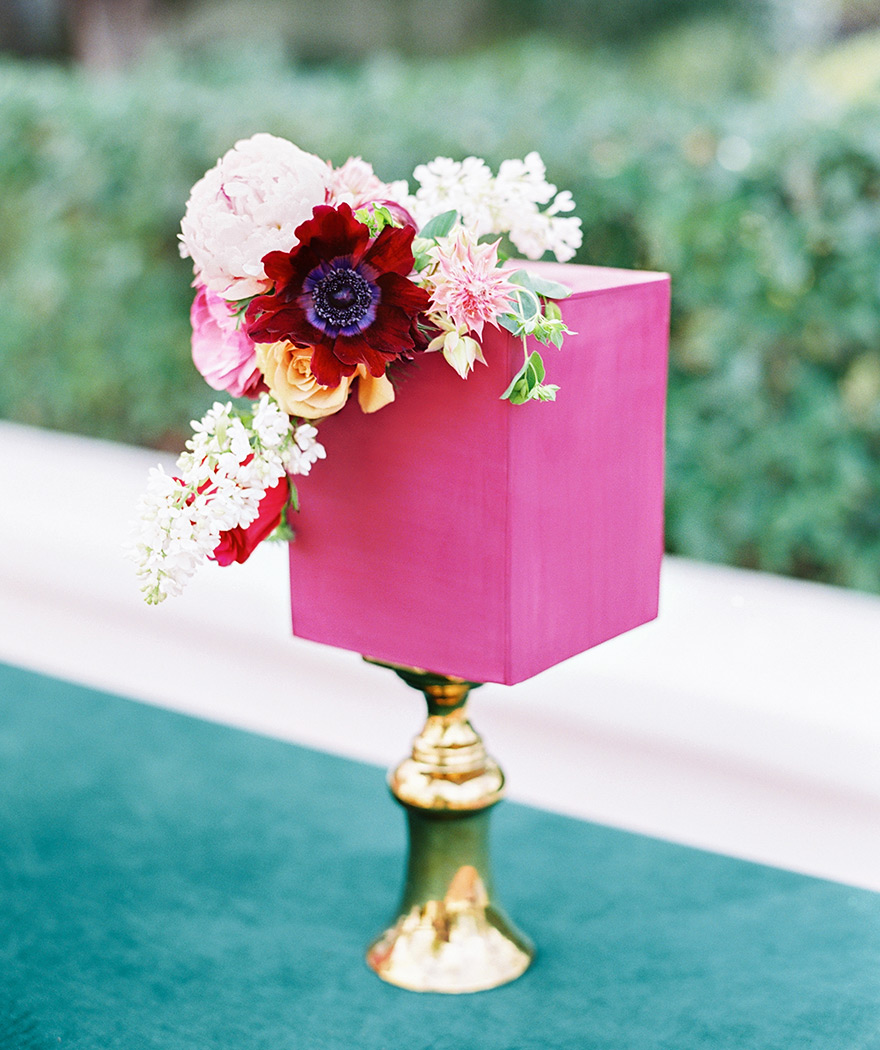Modern square wedding cake in vibrant fuchsia with fresh flowers