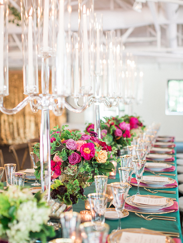 lush, green tablecloth, vibrant flowers, and modern glass candelabra