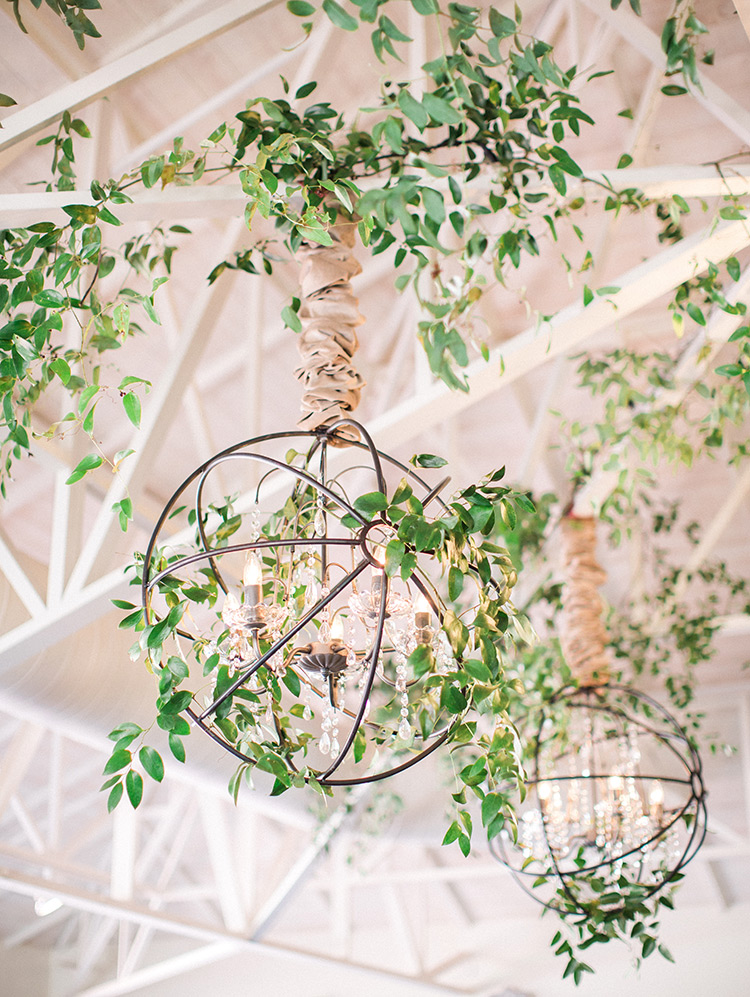 Greenery and metal surround chandeliers, wedding reception