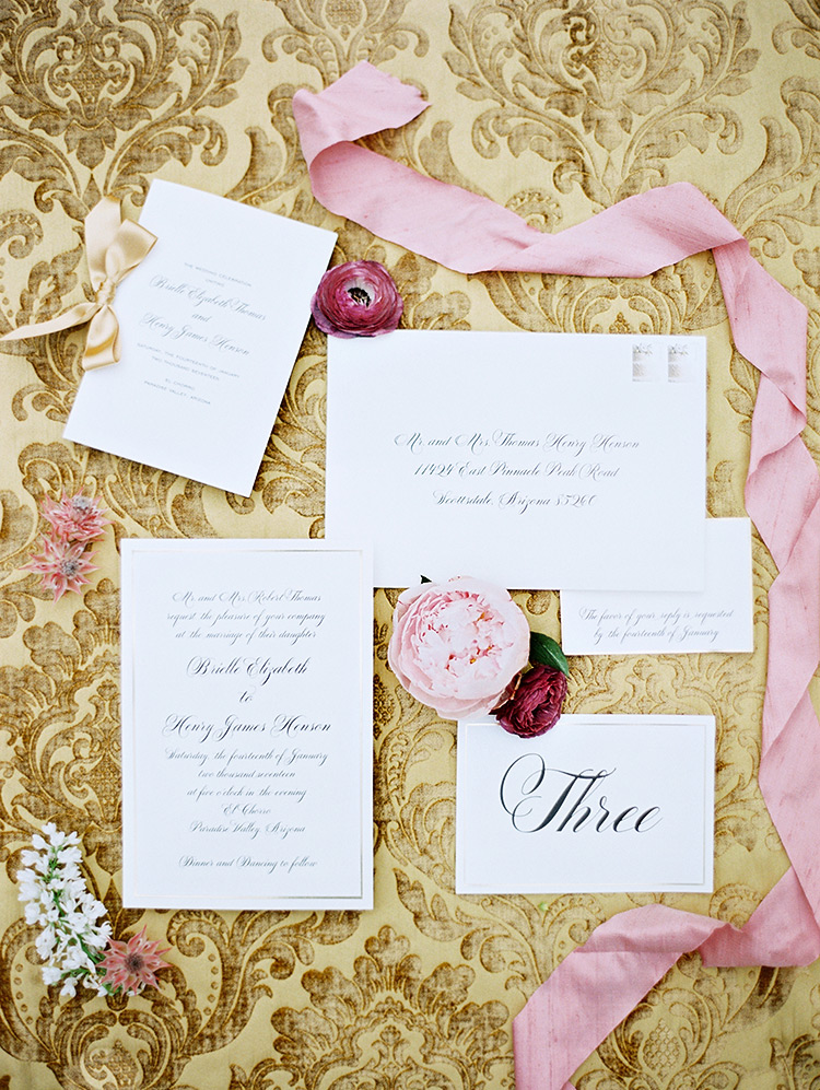 elegant wedding invitation against a gold velvet jacquard