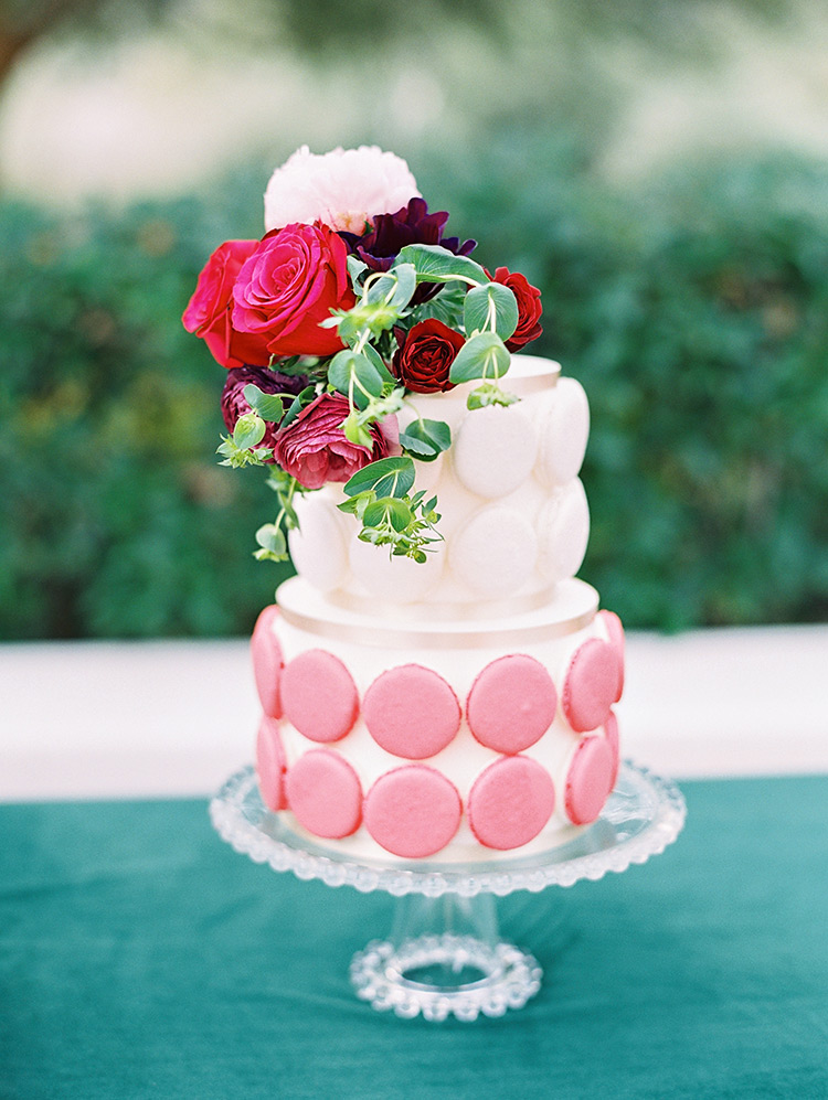 sweet pink wedding cake decorated with macarons and fresh flowers