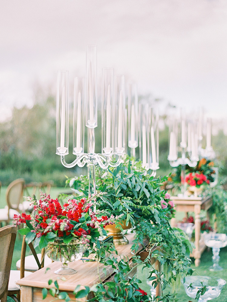 outdoor wedding ceremony with greenery and modern glass candelabra