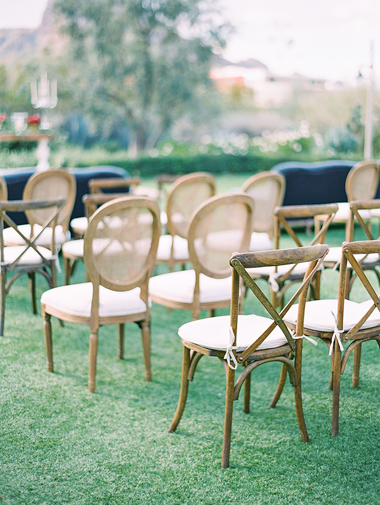 outdoor wedding ceremony with sofas and wooden chairs