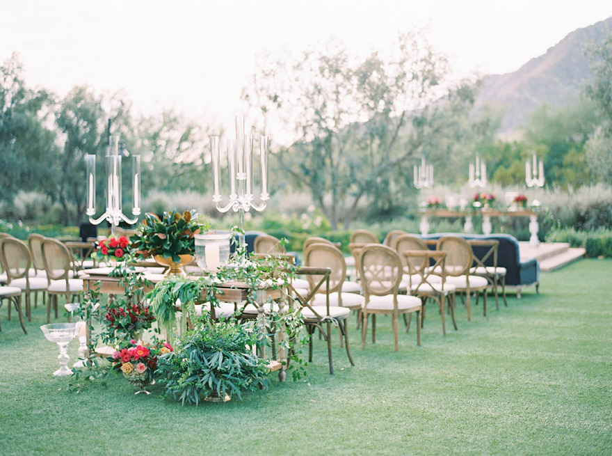Outdoor wedding reception full of candles and greenery