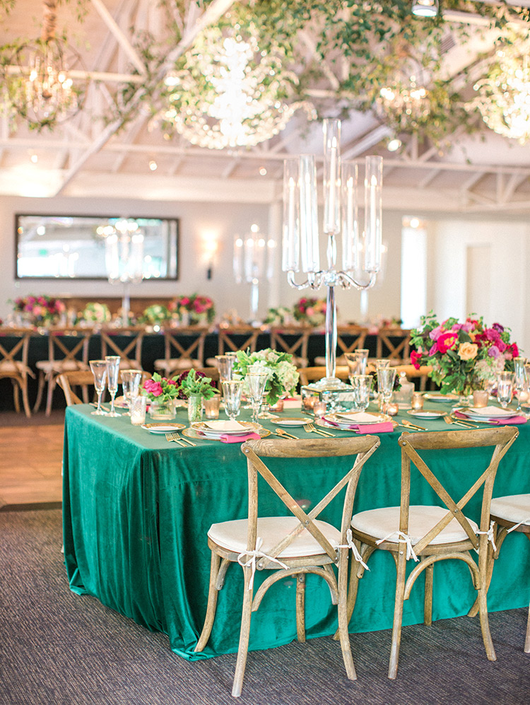 jewel toned wedding reception tablescape with forrest green velvet linens