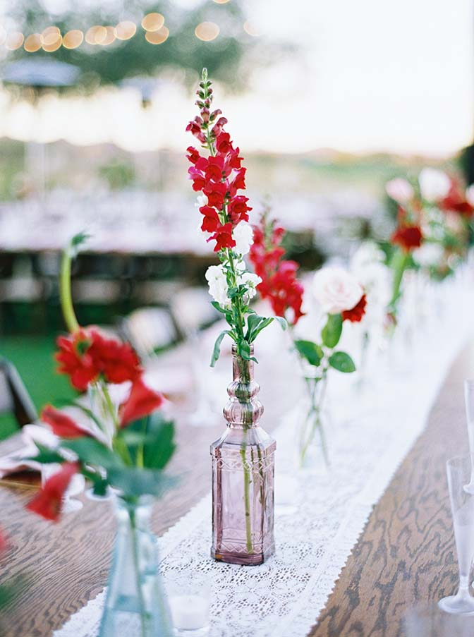outdoor celebration of long, wooden farm tables set with flowers