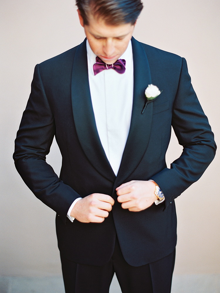 groom in a black tux with purple bow tie