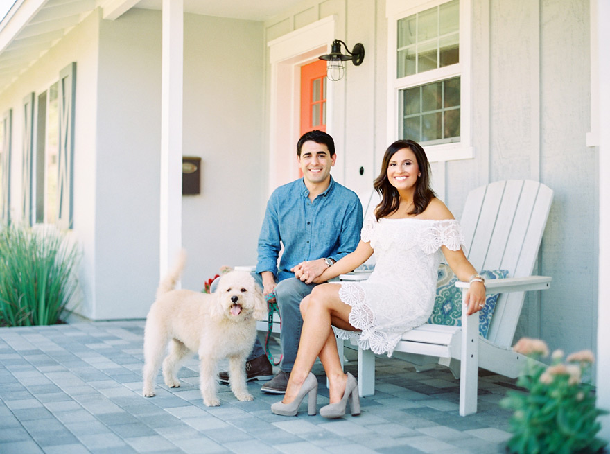 Stylish front porch with Adirondack chairs and an adorable dog