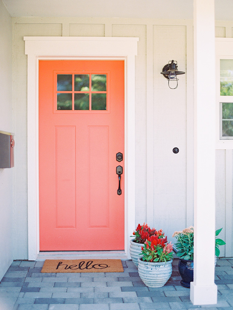 Charming front porch with a pink door and welcome mat