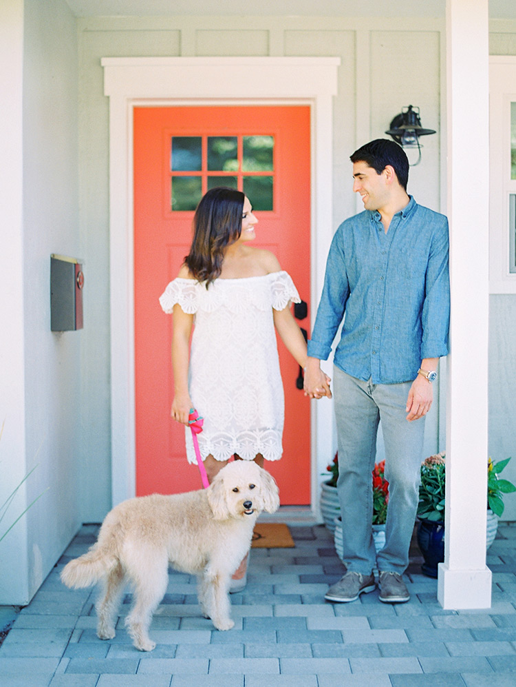 Happy couple and their labradoodle in front of their pink door