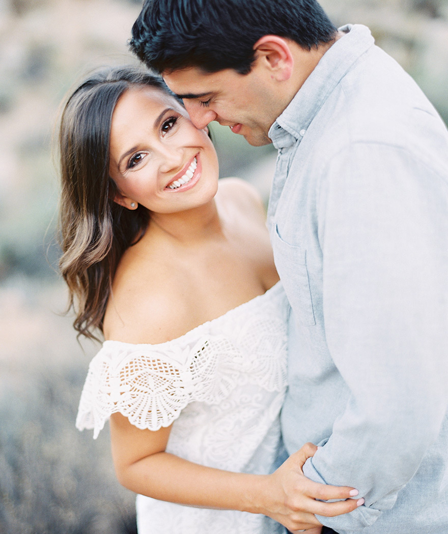 Loving couple in a desert engagement session, white lace dress