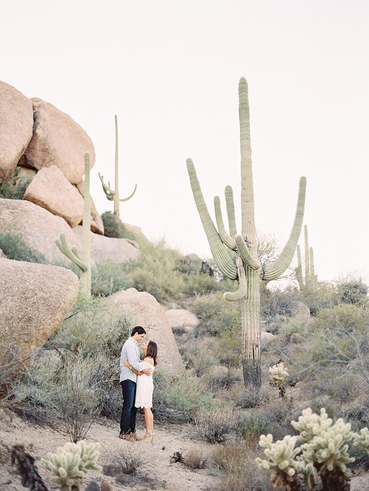 Loving couple in a desert engagement session, Saguaro cactus