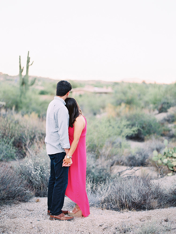 Loving couple look out over the desert, engagement photos