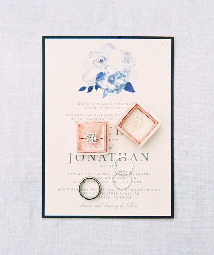 dazzling square engagement ring atop an invitation with watercolor touches