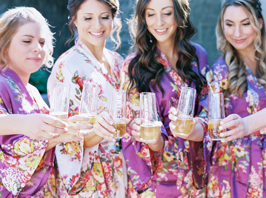 bridesmaids in floral robes toast with champagne
