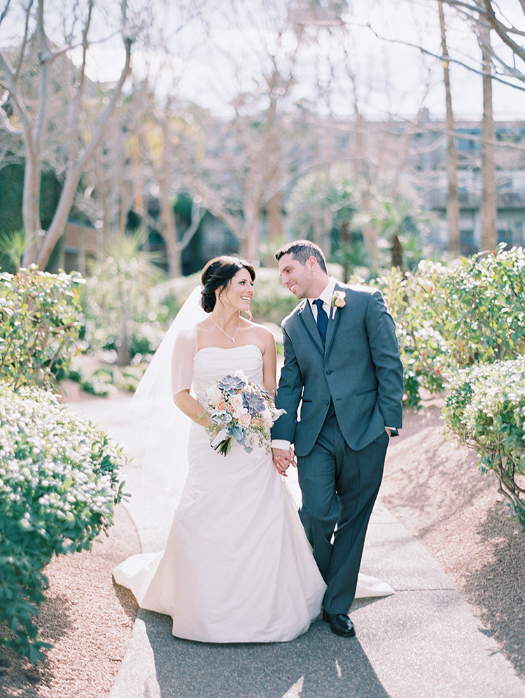 happy bride & groom walk hand-in-hand at Hyatt Scottsdale