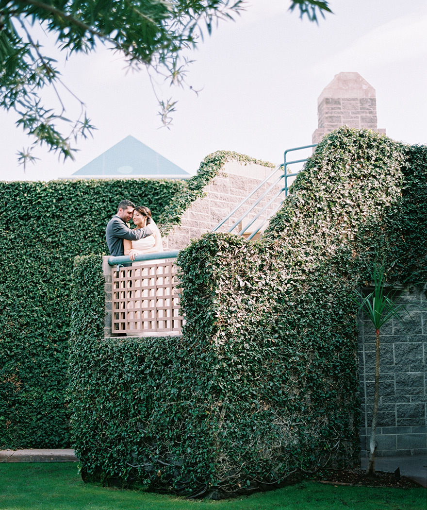 bride & groom embrace on an ivy-covered stairway